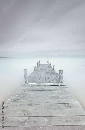 Poster Wooden pier on lake in a cloudy and foggy mood.