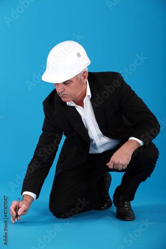 Engineer making markings on the floor