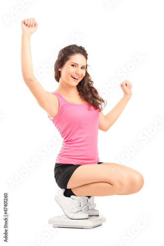 Happy female on a weight scale gesturing with her hands