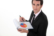 Man holding pie-chart and pen