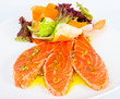 Slices of salmon with fresh vegetables and lettuce