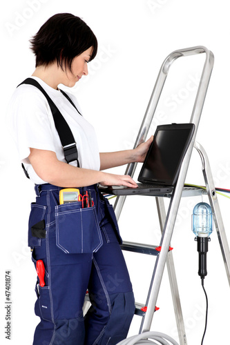 Female electrician resting laptop on rung of step-ladder