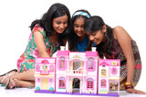 Girls looking into a dollhouse