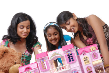 Girls looking into a doll house
