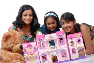 Girls playing with doll house