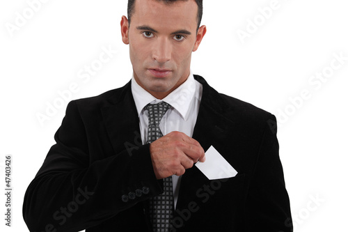 businessman putting a visit card in his pocket