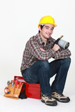 Tradesman holding a blowtorch and sitting on his toolbox poster