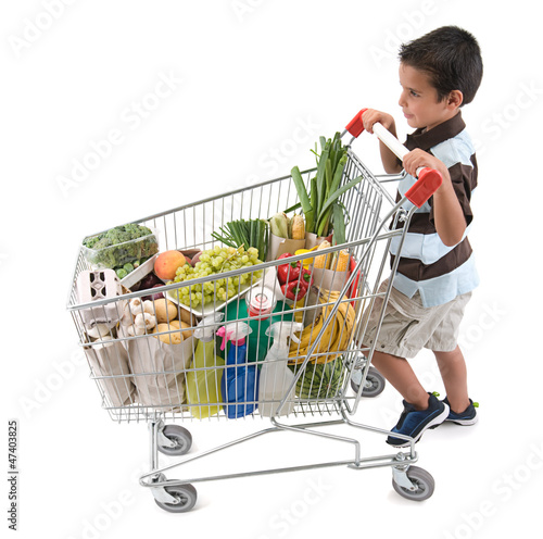 Cute boy walking with shopping trolley isolated on white