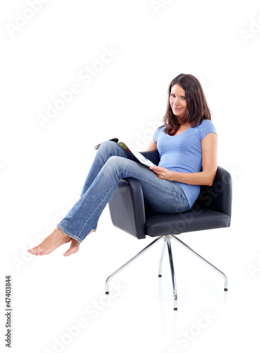 Young woman sitting in a chair with magazine