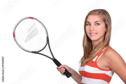 Female teenager holding tennis racket