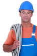 Tradesman carrying corrugated tubing around his shoulder