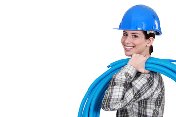 Female plumber carrying pipes