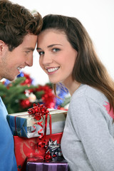 Couple stood by Christmas tree and gifts