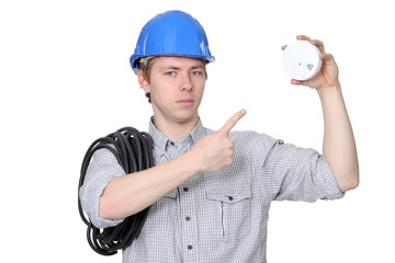 An electrician with a fire detector.