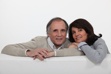 Mature couple leaning on back of sofa