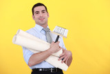 young handsome man carrying rolls of wallpaper