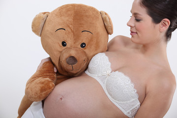 Pregnant woman holding a giant teddy bear