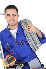 Worker carrying cabling coiled around his shoulder