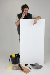 Tiler using cellphone and pointing to poster