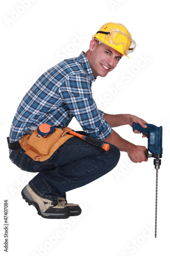 Tradesman using a power tool with a long bit