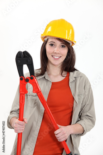 young female apprentice holding giant pliers