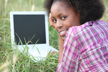 Woman laid in field in front of laptop computer