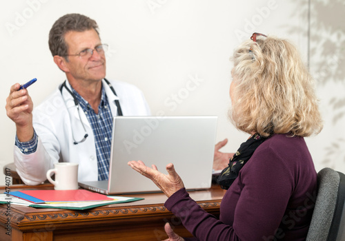 Male Doctor and Female Patient Consulting in office setting.