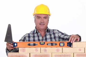 Bricklayer checking the level of a wall