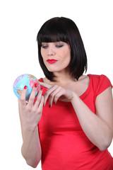 Brunette holding a miniature globe