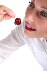 Woman about to bite a cherry