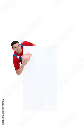 Manual worker stood with piggy-bank and blank poster