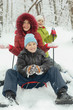 Mother, little son and daughter ride on sled in winter forest