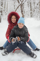 Mother, son ride on sled in winter forest, focus on child