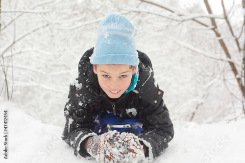 boy lie on snow and sculpt snowball in winter forest