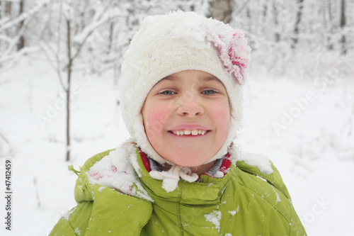 portrait of little girl in hat with snow in winter forest
