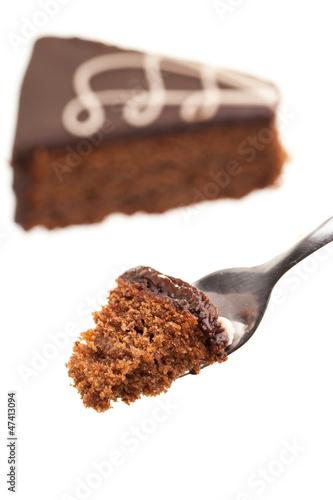 Kuchengabel mit Sachertorte im Hintergrund