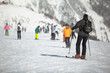Group of skiers on snowy hillslope, focus on nearest skier