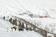 Group of skiers and snowboarders comes down the snowy hill