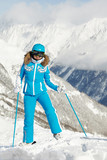 Young woman in blue ski suit stands