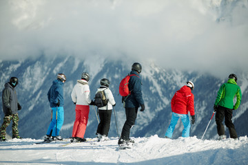 Group of young skiers stands on edge of snowy hillslope