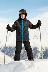 Boy in ski suit stands leaning on ski poles with blue sky