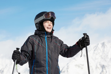 Smiling boy in ski suit against mountains and blue sky
