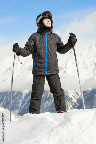 Boy in ski suit stands leaning on ski poles and looking upward,