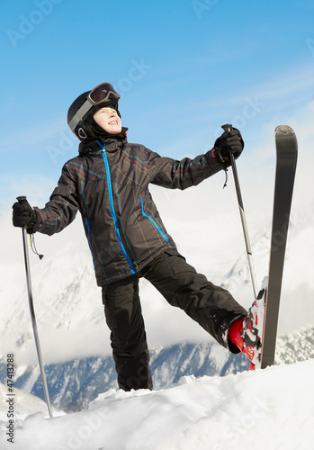 Boy in ski suit stands rising up one leg with ski and looking up