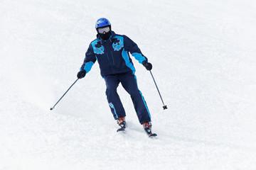 Man in darkblue ski suit glides downhill on skis