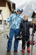 Father with snowboard and son with ski on street