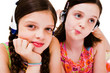 Close-up of girls listening music on headphones