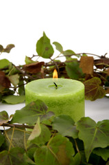 burning candle with circle green leaver