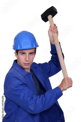 Man wielding sledge-hammer