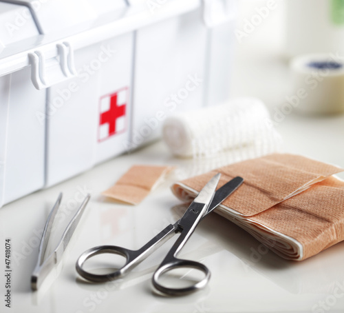 First aid kit with bandage and scissors on white table